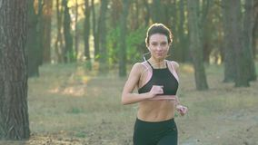 Close up of woman with headphones running through an autumn forest at sunset stock footage