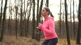 Close up of woman with headphones and smartphone running through an autumn forest at sunset stock video