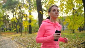 Close up of woman with headphones and smartphone running through an autumn park at sunset stock footage