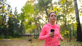 Close up of woman with headphones and smartphone running through an autumn park at sunset stock video footage
