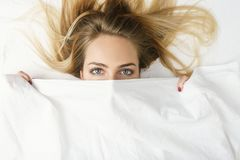 Close-up of a woman hiding in her bed at home. Top view of attractive young woman covering half of her face with sheets and looking at camera while lying on the Stock Photography