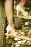 Close up of woman in high heels climbing up ladder Stock Photo