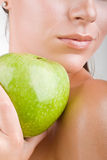 Close-up woman holding an apple. On light background (focus on the apple Stock Photography
