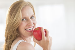 Close-Up Of Woman Holding An Apple In House Stock Image