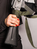 Close up of woman holding an automatic assault rifle Royalty Free Stock Image