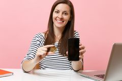 Close up of woman holding bitcoin metal coin of golden color, future currency and mobile phone with blank empty screen royalty free stock photos