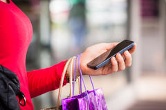 Close-up of woman holding cell phone. A close-up shot of a woman holding a cell phone or mobile phone whilst out shopping royalty free stock photography