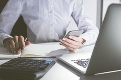 Close up of woman holding cell phone and taking notes. Close up of woman's hands with cell phone and pen. She is sitting near her laptop and taking notes looking Stock Images
