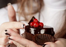 Close-up of a woman holding a chocolate cake with red berry Royalty Free Stock Images
