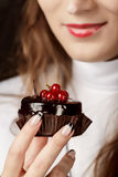 Close-up of a woman holding a chocolate cake with red berry Stock Photography