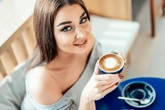 Close up of woman looking at camera, holding cup of coffee. stock photos