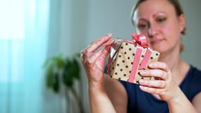 Close-up of a woman holding a gift. She Packed it herself, smiling and looking. Selective focus stock video footage