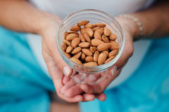 Close Up Of Woman Holding glass bowl with Almonds nuts. Royalty Free Stock Images
