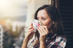 Woman is drinking coffee on a balcony and enjoying city view. Close up of a woman holding in hands and drinking cup of coffee. Early morning routine Royalty Free Stock Photos