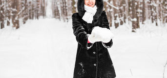 Close-up of woman holding natural soft white snow in her hands to make a snowball, smiling during a cold winter day in Royalty Free Stock Photography