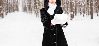 Close-up of woman holding natural soft white snow in her hands to make a snowball, smiling during a cold winter day in Stock Photos