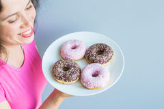 Close-up of woman holding plate with delicious sweet donuts Stock Image