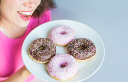 Close-up of woman holding plate with delicious sweet donuts Stock Photography