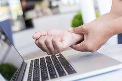Woman holding and pressing or touching her wrist while working w Royalty Free Stock Photography