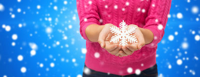 Close up of woman holding snowflake decoration Royalty Free Stock Photo
