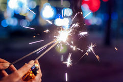 Close up of woman holding sparkler at night. Royalty Free Stock Images