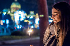 Close up of woman holding sparkler on the street. Girl with spar Royalty Free Stock Image