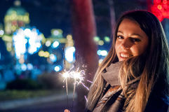 Close up of woman holding sparkler on the street. Girl with spar Stock Images
