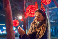 Close up of woman holding sparkler on the street. Young smiling girl holding sparkler in her hand Royalty Free Stock Image