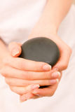 Close-up of a woman holding stones. In spa Stock Images