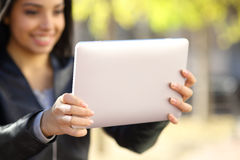 Close up of a woman holding and watching a digital tablet. In a park stock image