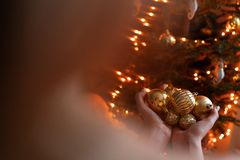 Close-up woman holds in the hands of Golden Christmas tree toys. Winter holidays in a house interior. Golden and white. Happy young woman decorating christmas royalty free stock images