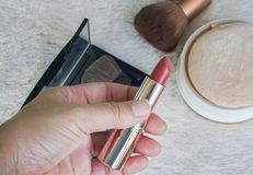 Woman holds lipstick in nude color in left hand for make-up with powder with brush backdrop royalty free stock image
