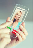 Close up of woman with incoming call on smartphone. Business, technology and people concept - close up of women hand holding and showing transparent smartphone stock photography