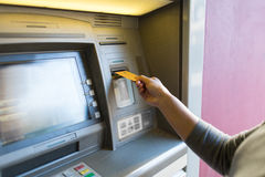Close up of woman inserting card to atm machine Royalty Free Stock Photo