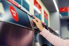 Woman inserting coin in self service washing machine close-up royalty free stock image