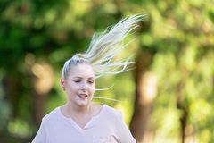 Close Up Of Woman Jogging. And hair flying in soft late afternoon light and beautiful background royalty free stock photo