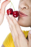 Close-up of a woman kissing a couple of cherries. Close-up of a woman holding and kissing a couple of red ripe cherries Royalty Free Stock Images