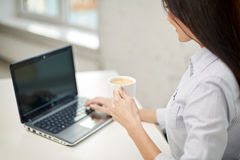 Close up of woman with laptop drinking coffee Stock Images