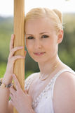 Close up of woman leaning against wooden post Royalty Free Stock Photo