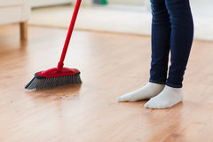 Close up of woman legs with broom sweeping floor. People, housework, cleaning and housekeeping concept - close up of woman legs with broom sweeping floor at home stock photos