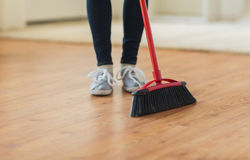 Close up of woman legs with broom sweeping floor Royalty Free Stock Image