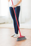 Close up of woman legs with broom sweeping floor Stock Photography