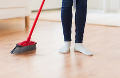 Close up of woman legs with broom sweeping floor. People, housework, cleaning and housekeeping concept - close up of woman legs with broom sweeping floor at home Royalty Free Stock Image