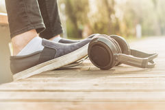Close-up of woman legs relaxing outside near headphones Stock Image