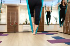 Close up Woman legs stay in hammock doing fly yoga stretching exercises in gym. Fit and wellness lifestyle.  royalty free stock photos