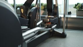 Close-up of woman legs using an elliptic trainer in a fitness center. Lifestyle concept. Steady cam shot stock video