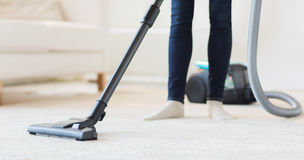Close up of woman legs with vacuum cleaner at home. People, housework and housekeeping concept - close up of woman with legs vacuum cleaner cleaning carpet at stock photography