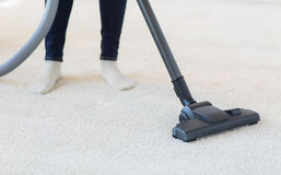 Close up of woman legs with vacuum cleaner at home Royalty Free Stock Photography