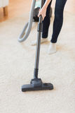 Close up of woman legs with vacuum cleaner at home Stock Images