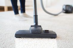 Close up of woman legs with vacuum cleaner at home Stock Photo